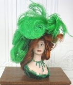 Green Feathered Hat on Red Haired Mannequin by Pat Stevens